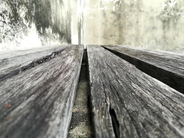 Vecchio pavimento di legno e vecchia fine del fondo del muro di cemento su