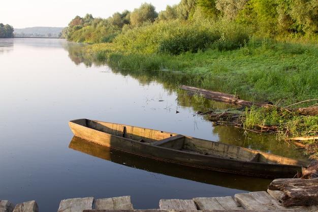 Vecchio peschereccio di legno ancorato dalla sponda verde del fiume