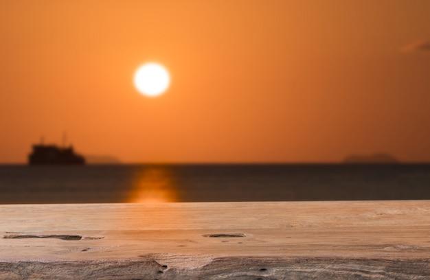 Vecchio piano d'appoggio di legno con il fondo di tramonto del mare