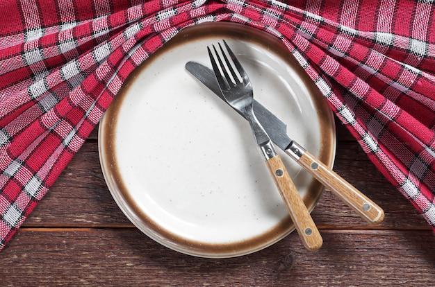 Vecchio piatto, forchetta e coltello vuoti con la tovaglia