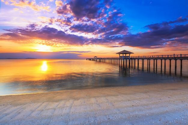 Vecchio pilastro del ponticello di legno contro il bello cielo di tramonto