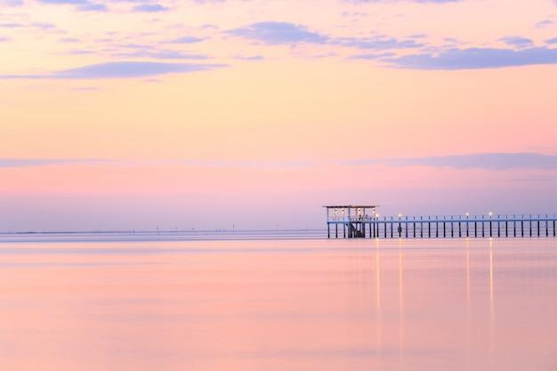 Vecchio pilastro di legno del ponte contro bello uso del cielo di tramonto per sfondo naturale