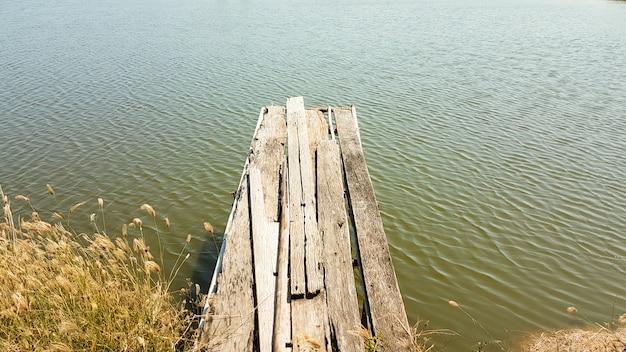 Vecchio ponte di legno sulla riva dello stagno