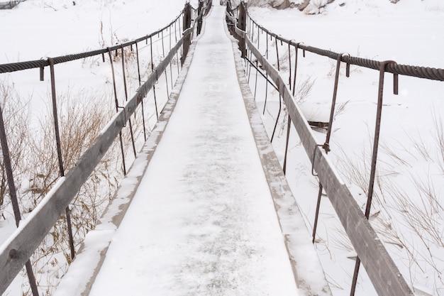 Vecchio ponte innevato stretto sopra il fiume congelato