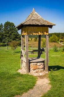 Vecchio pozzo in legno. paesaggio estivo. vista rurale
