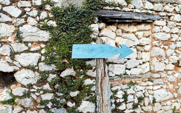 Vecchio puntatore a destra su uno sfondo di un muro di pietra