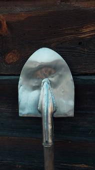 Vecchio puntello arrugginito della pala su contro la vecchia parete di legno, struttura di legno