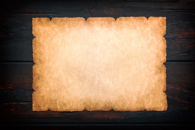 Vecchio rotolo d'annata della carta di struttura del fondo di lerciume su fondo di legno scuro