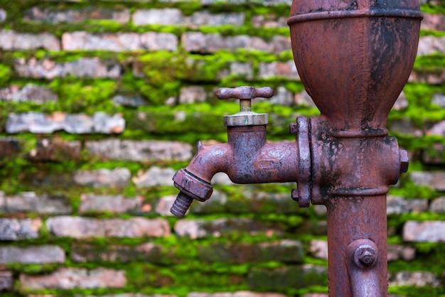 Vecchio rubinetto arrugginito con il vecchio muro di mattoni e l'erba del muschio