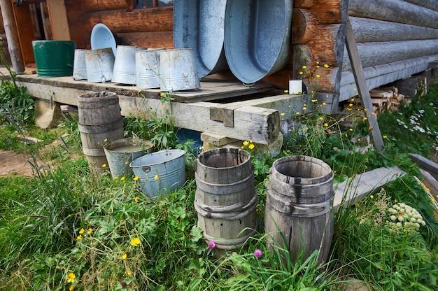 Vecchio secchio di legno vicino ad una casa di legno nelle montagne