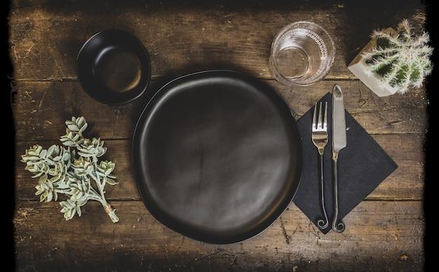 Vecchio tavolo in legno con piatti e decorazioni su di esso sotto le luci