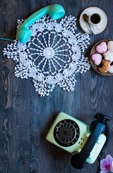 Vecchio telefono d'annata con le ciambelle del caffè di biscotti su un fondo di legno