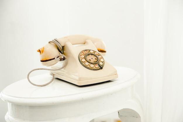 Vecchio telefono del telefono dell'annata sulla priorità bassa della stanza bianca.