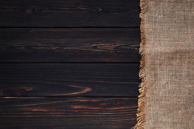 Vecchio tessuto di tela da imballaggio su fondo di legno scuro
