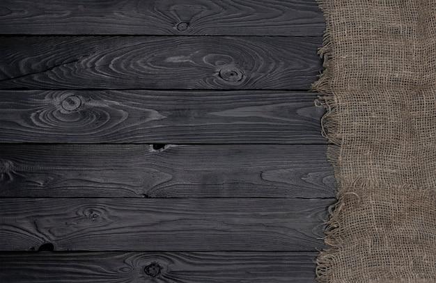 Vecchio tovagliolo del tessuto della tela da imballaggio sulla vista superiore e di legno nera