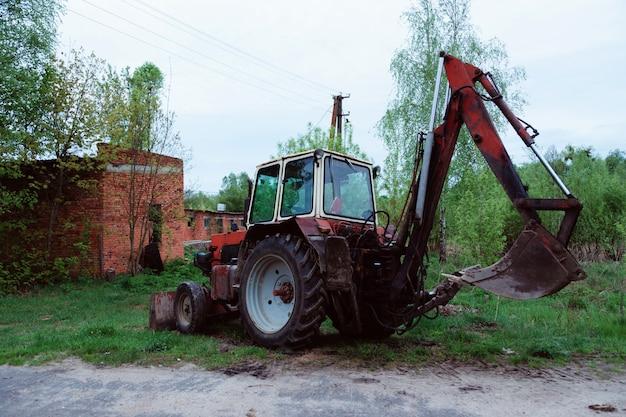 Vecchio trattore arrugginito rosso in un campo vicino alla strada