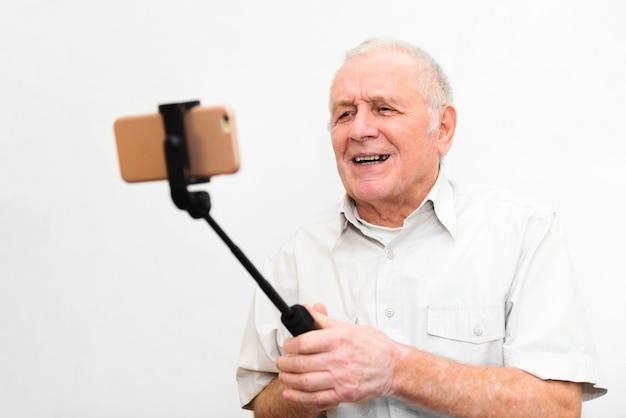 Vecchio uomo attivo prendendo selfie con il cellulare isolato su sfondo grigio
