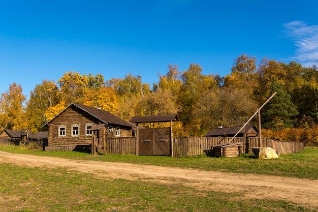 Vecchio villaggio in russia. casa con staccionata in legno e pozzo.
