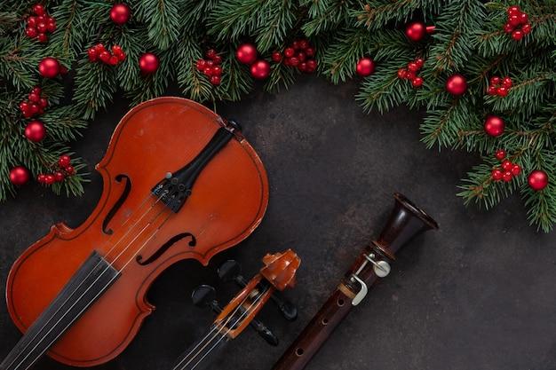 Vecchio violino e flauto con rami di abete con decorazioni natalizie. vista dall'alto, primo piano