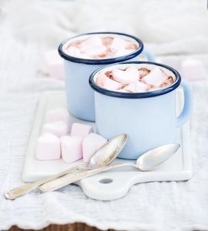 Vedi il set di auguri di san valentino. caramelle gommosa e molle a forma di cuore e di cioccolata calda in vecchie tazze dello smalto sul bordo di servizio di ceramica bianco