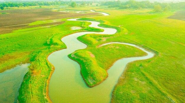 Veduta aerea del canale tra i prati e terreni agricoli nel tempo tramonto.