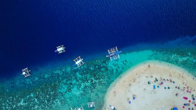 Veduta aerea della spiaggia sabbiosa con i turisti che nuotano in bella acqua cristallina della spiaggia dell'isola di sumilon che atterra vicino a oslob, cebu, filippine. - aumentare la lavorazione del colore.