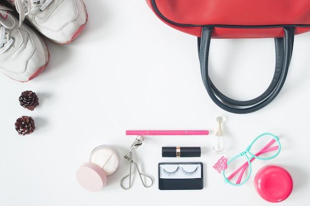 Veduta aerea di elementi essenziali di bellezza, vista superiore di borsa a mano rossa, occhiali da vista, cosmetici e scarpe da ginnastica, vista dall'alto isolato su sfondo bianco