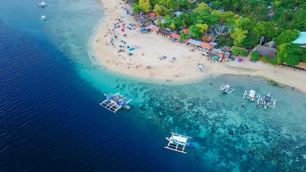 Veduta aerea di spiaggia sabbiosa con turisti che nuotano in bella acqua cristallina della spiaggia dell'isola di sumilon che atterra vicino a oslob, cebu, filippine. - aumentare la lavorazione del colore.