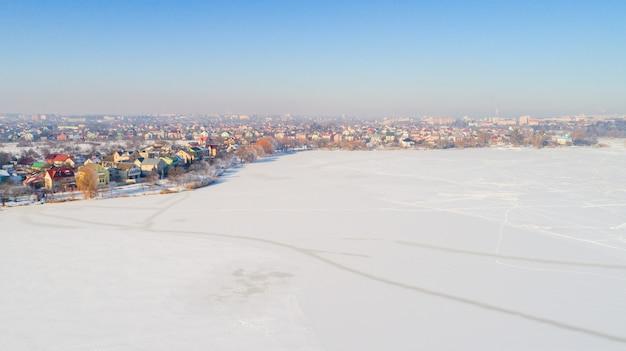 Veduta aerea invernale dall'alto in alto sopra la vita rurale rallentata dal piccolo fiume.