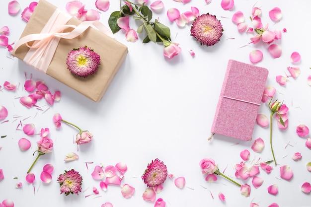 Veduta dall'alto dei fiori; confezione regalo e diario su superficie bianca