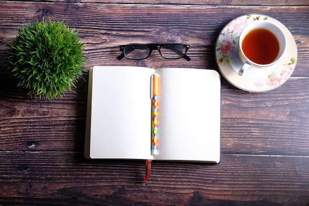 Veduta dall'alto del diario aperto, tè e occhiali sul tavolo