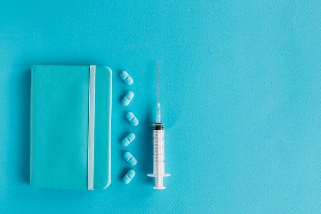 Veduta dall'alto del diario; pillole e siringhe su sfondo blu