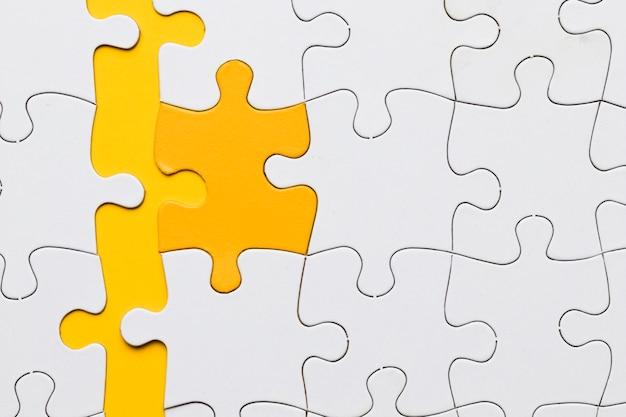 Veduta dall'alto del pezzo di puzzle giallo organizzato con pezzi bianchi