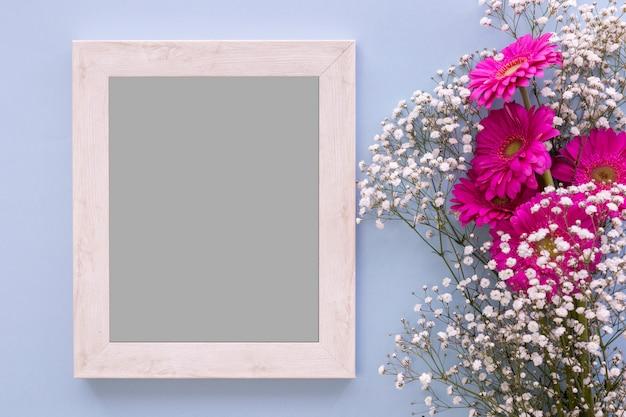 Veduta dall'alto della cornice vuota con fiori rosa e respiro del bambino