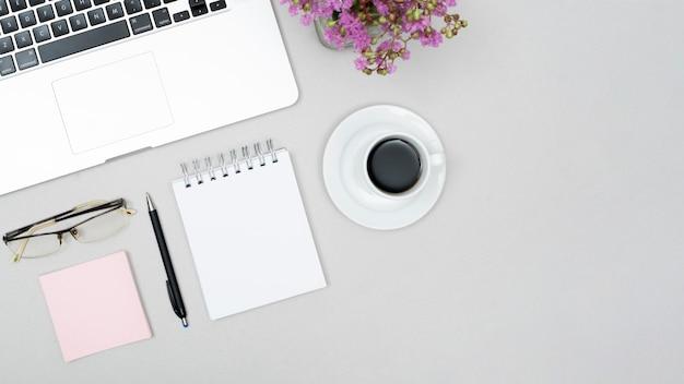 Veduta dall'alto della tazza di caffè; il computer portatile; occhiali da vista; pot di fiore del blocco note a spirale sulla tabella grigia