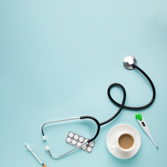 Veduta dall'alto dello stetoscopio; tazza di caffè; compresse; termometro; iniezione sopra la scrivania blu