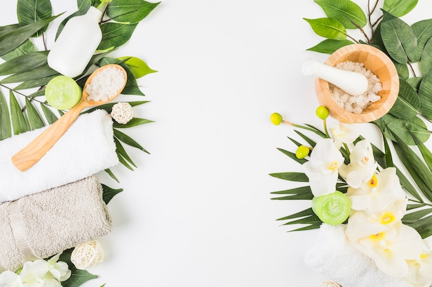 Veduta dall'alto di asciugamani; sale; candele; fiori e foglie su superficie bianca