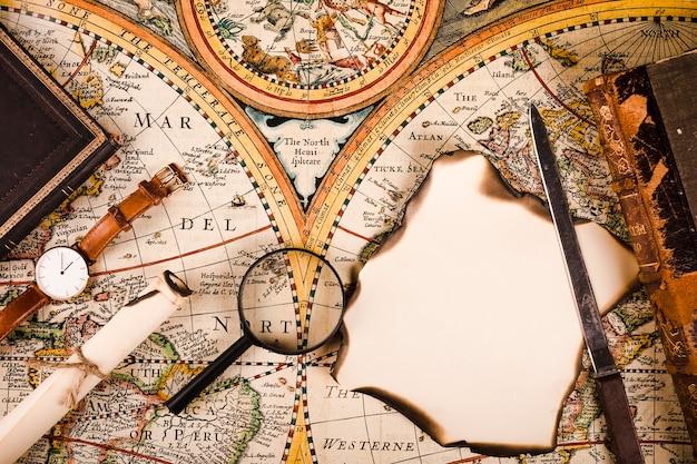 Veduta dall'alto di orologio da polso, lente d'ingrandimento, carta bruciata e coltello sulla mappa