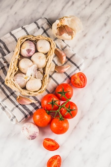 Veduta dall'alto di pomodori rossi; cipolle; spicchi d'aglio e stoffa sulla superficie del marmo