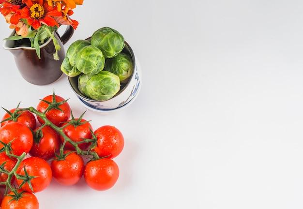 Veduta dall'alto di pomodori succosi; cavoletti di bruxelles e fiori su sfondo bianco