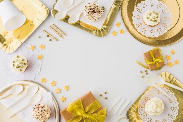 Veduta dall'alto di regali di compleanno; cupcake e candele su sfondo bianco