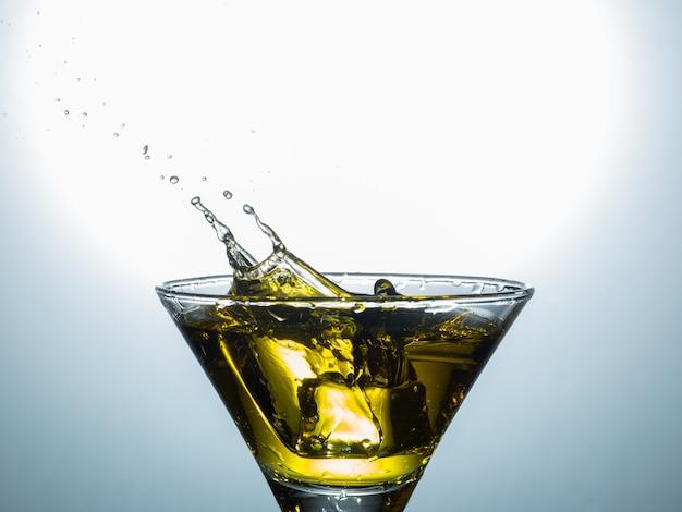 Veduta di martini glass spruzzata dal cubetto di ghiaccio.