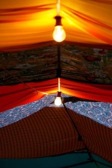 Veduta di una fiera di strada dove il soffitto è composto da pezzi di stoffa cuciti di vari colori.