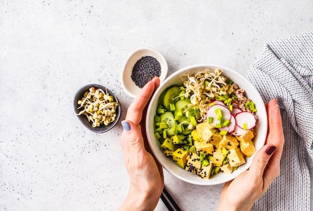 Vegan poke bowl con tofu in salamoia, verdure e riso in una ciotola bianca, vista dall'alto.