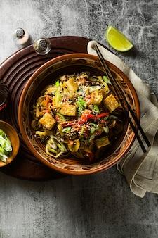 Vegano asiatico saltato in padella con tofu, spaghetti di riso e verdure, vista dall'alto.