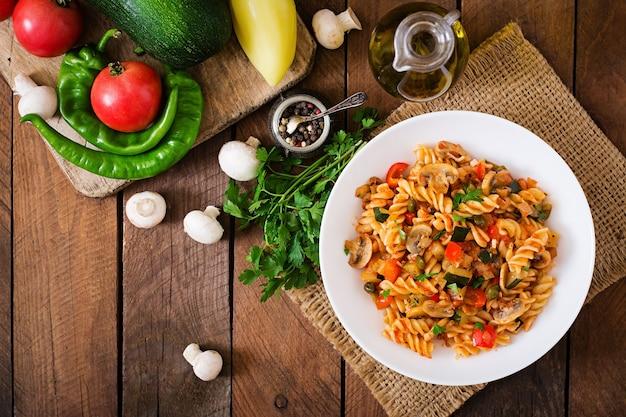 Vegetariano pasta vegetale fusilli con zucchine, funghi e capperi in ciotola bianca sul tavolo di legno