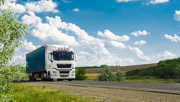 Veicolo camion europeo con contenitore su autostrada e cielo blu con nuvole.