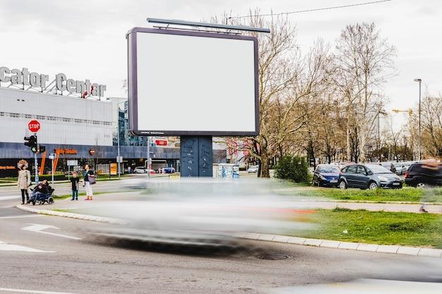 Veicolo offuscata che passa dal tabellone per le affissioni in bianco sulla strada