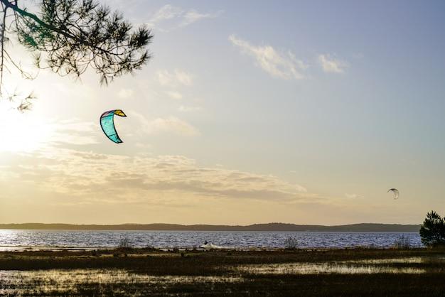 Vela di kitesurf nell'alba kitesurfing del lacanau del lago beach della spiaggia di tramonto di sera in francia