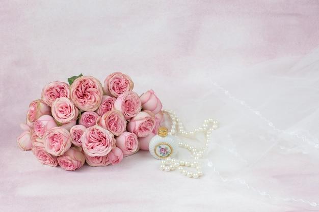 Velo, perle, una bottiglia di profumo e un bouquet di rose rosa